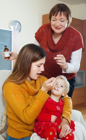 Young woman with mature mother caring for sick toddler at home photo