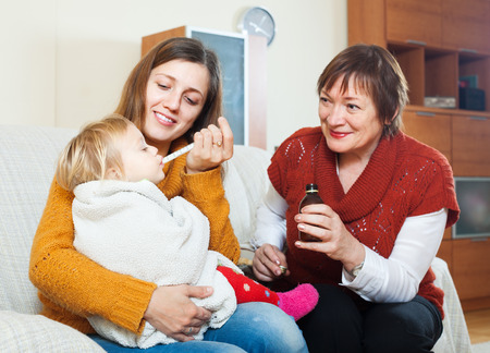 sick baby:  woman with mature mother caring for sick baby at home. Focus on toddler Stock Photo