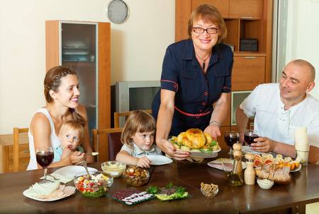 Happy multigeneration family with chicken at home interior Stock Photo