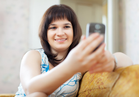ordinary woman: ordinary woman reads SMS in mobile at home