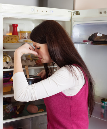 frowy: Brunnette  woman holding her nose because of bad smell from food near refrigerator  at home Stock Photo