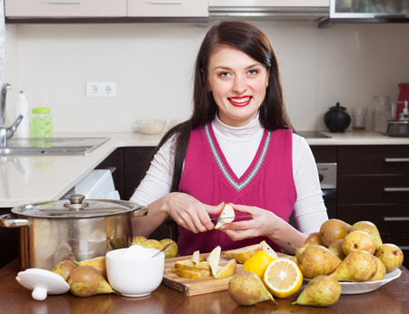Woman cutting pears for pear jam in kitchen photo