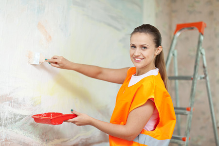 housepainter: Smiling woman in uniform paints wall with brush