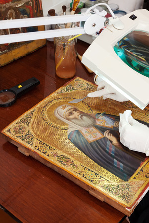 restoration of ancient gilded icon with  filling knife at workshop photo