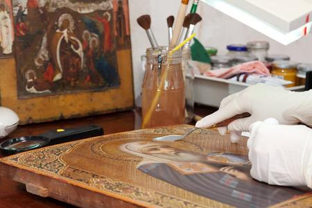 estoration of old icon with  filling knife at restoration workshop photo