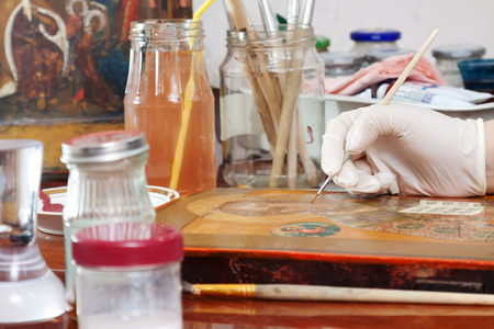 restoration of old icon with thin brush at workshop photo