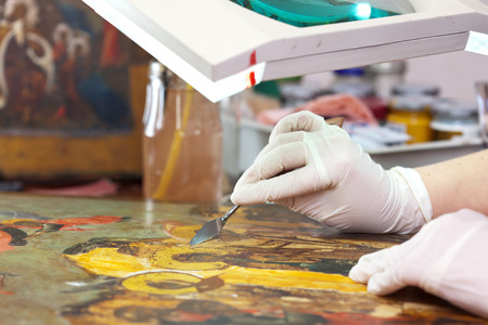 restoring: accurate cleaning old Christian icon with palette knife at restoration workshop