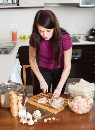 nutricion:  woman cooking  noodles with seafood in home kitchen