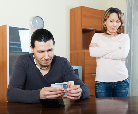 Money in family. Man counting cash, woman watching him Stock Photo