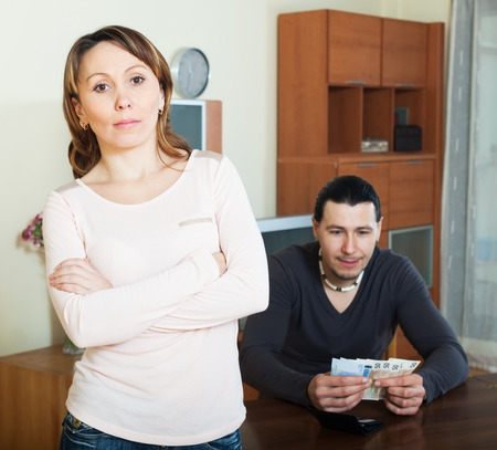 covetous: Financial problems in family. Man counting currency, woman watching him in home