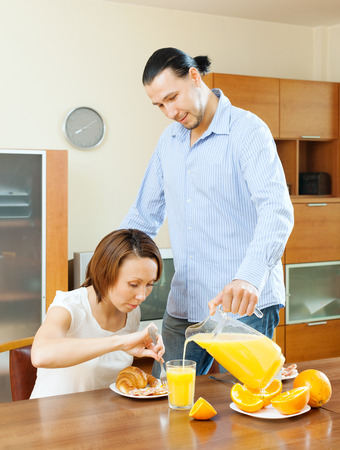 couple having breakfast with juice in morning at home photo