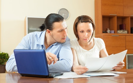 couple staring financial documents at table in home interior photo