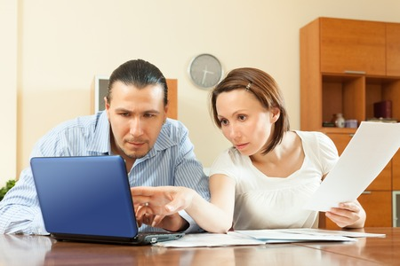 Young family  with financial documents at home interior photo
