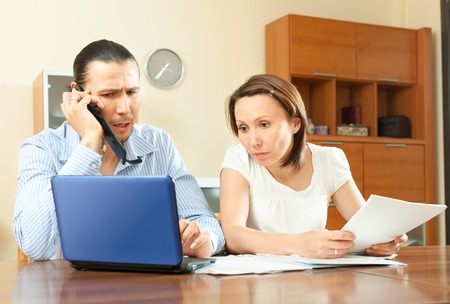 serious couple looking financial document at home photo