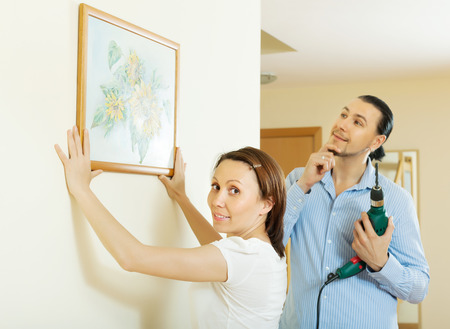 modifying:  couple choosing point for picture in the wall at home