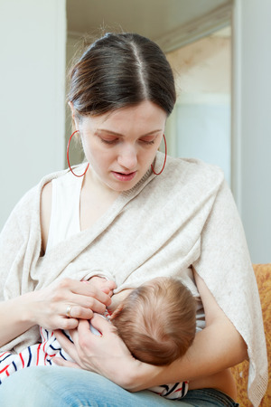 Mother breast feeding her three-month baby at home interior photo