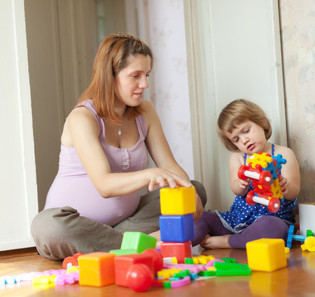 pregnant mother plays with child in home interior photo