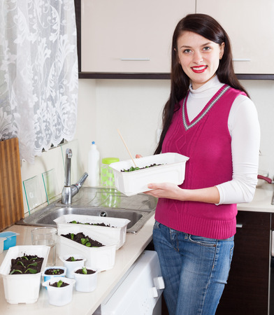 Happy woman with various sprouts at home kitchen photo