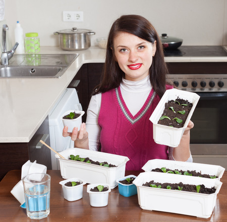 Happy brunette girl working with  seedlings   photo