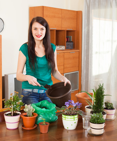 Happy woman transplanting potted flowers at home photo