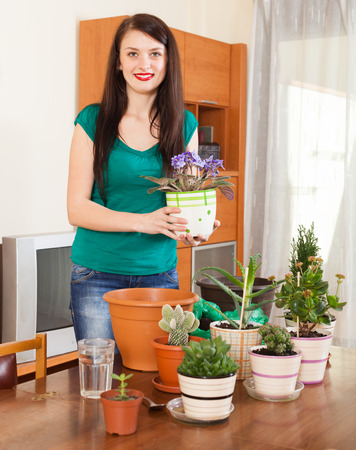 Smiling girl working with  viola flowers in pots   in home photo