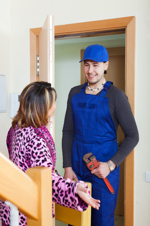 Middle-aged housewife meeting smiling service worker at the door at home photo