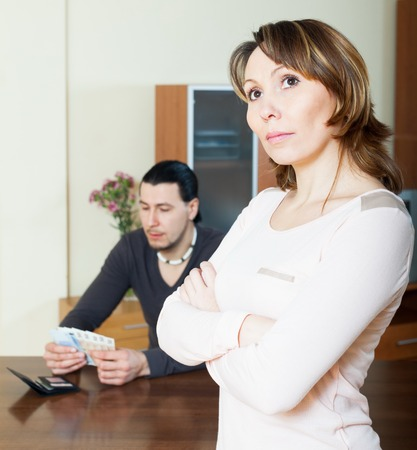 covetous: Sad woman against husband with money