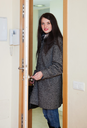 woman in coat loocking door lock and leaving her home photo