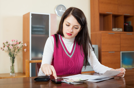 parsimony: serious brunette woman calculating the family budget