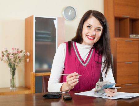 utility payments: Happy brunette girl with money and documents  in home interior Stock Photo