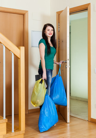 Brunette woman taking away the garbage out home photo