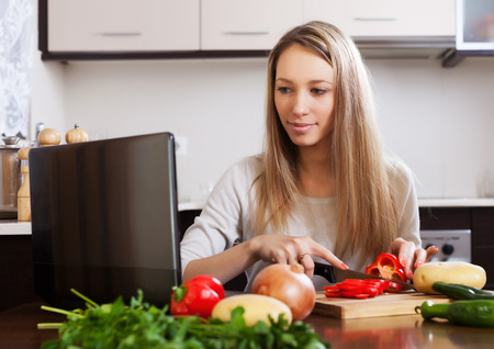 woman cooking with laptop in home kitchen photo