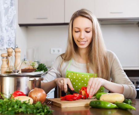 Smiling blonde woman in apron slicing  pepper at table in home kitchen photo