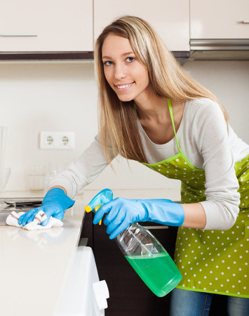 Blonde woman in apron cleaning  furniture with detergent in kitchen at home photo