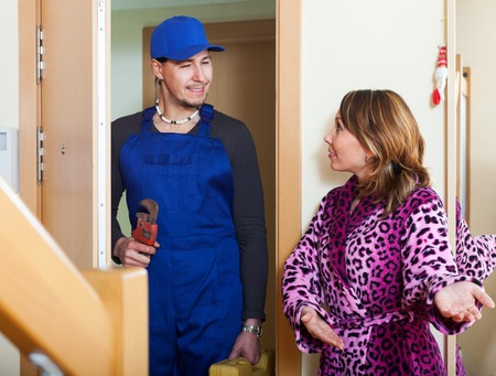 Middle-aged woman meeting worker in uniform at home photo