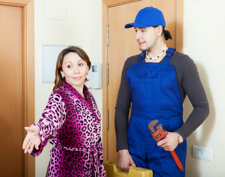 cheerful service worker in uniform came to call the young housewife photo