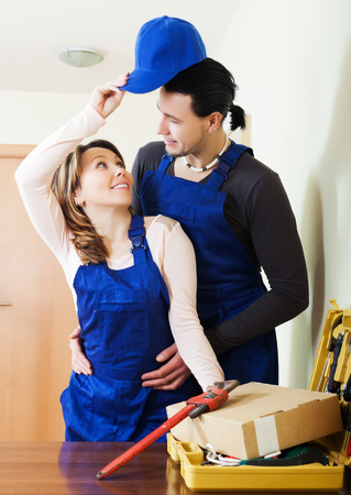 Technicians in uniform having flirt in the flat photo