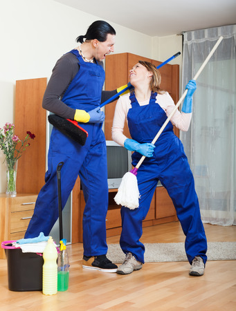 Playful man and woman cleaning room photo