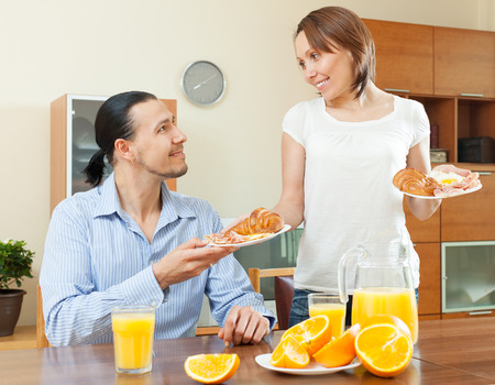 bacon portrait: Smiling woman serves breakfast her beloved man in morning