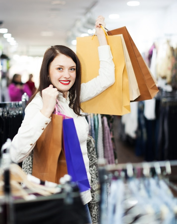 Ordinary girl buyer with shopping bags at clothing store photo