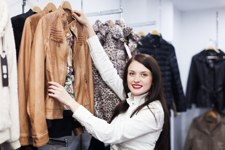 Ordinary fermale customer choosing jacket at clothing store
