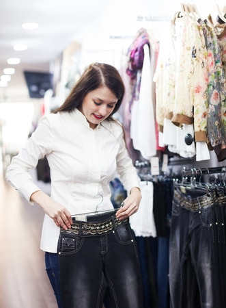 hellion: Young woman choosing trousers at clothing market