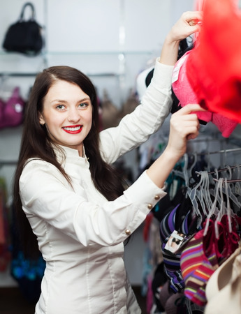 Ordinary girl choosing bra at clothing store  photo