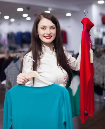 kledingwinkel: Brunette  woman choosing clothes at clothing store
