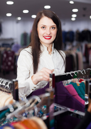 Happy female buyer choosing clothes at fashionable shop photo