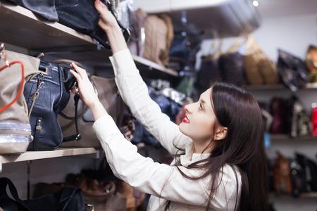 Young woman chooses bag at shop photo