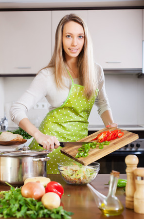 housewife in apron cooking with vegetables in home kitchen photo