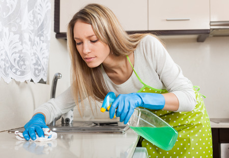 Ama de casa rubia limpieza de muebles en cocina con detergente