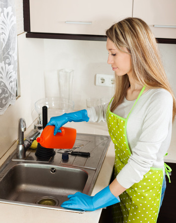 Young housewife cleaning pipe with detergent in kitchen at home photo