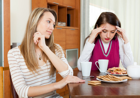 fracas: Two women  after conflict at table in home Stock Photo